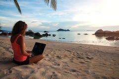 Playa de la muchacha del ordenador portátil independiente foto de archivo