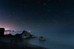 Playa de la noche debajo de rastros de la estrella Imágenes de archivo libres de regalías