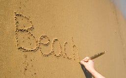 Playa de la palabra escrita en la arena Fotos de archivo
