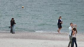 playa de la primavera 4K, día ventoso La gente está caminando a lo largo de la playa almacen de video