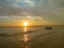 Playa de la puesta del sol con la silueta del barco del pescador adentro Imagen de archivo libre de regalías