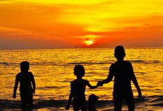 Playa de la puesta del sol con los niños jovenes Foto de archivo libre de regalías