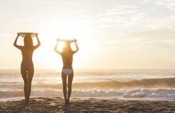 Playa de la puesta del sol de las personas que practica surf y de las tablas hawaianas de las mujeres del bikini Fotos de archivo libres de regalías
