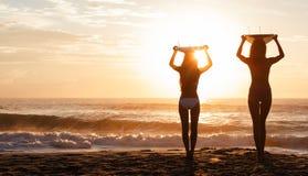 Playa de la puesta del sol de las personas que practica surf y de las tablas hawaianas de las mujeres del bikini foto de archivo libre de regalías