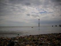 Playa de la tabla con el mar tranquilo y el rompeolas Fotografía de archivo
