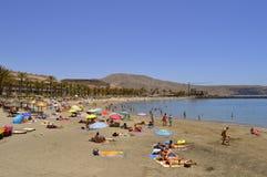 Playa De Las Americas sätter på land turister på stranden som tycker om set Arkivfoton