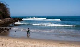 Playa de las personas que practica surf Fotografía de archivo