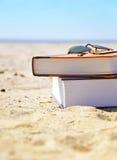 Playa de las vacaciones con los libros en arena Fotos de archivo libres de regalías