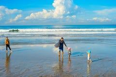 Playa de los niños de la familia de las personas que practica surf bali Fotografía de archivo libre de regalías