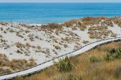Playa de madera de la arena del paseo marítimo sobre horizonte de la costa de mar Foto de archivo