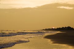 Playa de oro en la puesta del sol. Fotografía de archivo libre de regalías