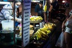 PLAYA DE PATONG, TAILANDIA - 19 DE MAYO DE 2017: Vida nocturna en Tailandia Comida de la calle A prepara una crepe con el chocola Imágenes de archivo libres de regalías