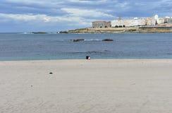 Playa de Riazor con el viejo hombre y la niña que se sientan en la arena Puesta del sol, día lluvioso, La Coruna, España imágenes de archivo libres de regalías