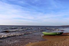 Playa de Riga, Letonia, 2014: Barco de pesca verde en una playa arenosa por el mar Imagen de archivo libre de regalías