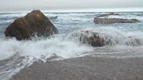 Playa de Sandy con el mar agitado picado, rocas amarillas, nubes grises densas que cubren el cielo almacen de video