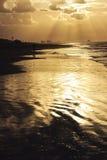 Playa de Sandy con las ondas y puesta del sol de oro imagen de archivo libre de regalías