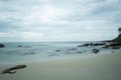 Playa de Sandy con las rocas en el mar y las nubes mullidas en el cielo Imagenes de archivo