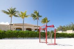 Playa de Sandy con un poste en él y palmeras en el fondo fotografía de archivo libre de regalías