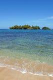 Playa de Sandy con la isla unspoiled imagen de archivo