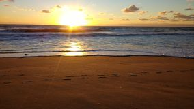 Playa de Sandy en la puesta del sol Imagen de archivo libre de regalías