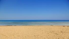 Playa de Sandy, mar tranquilo, fondo del cielo azul del claro Destino del verano foto de archivo