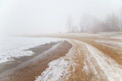 Playa de Sandy por el río en la niebla en invierno Imagen de archivo libre de regalías