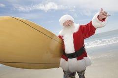 Playa de Santa Claus With Surf Board On foto de archivo libre de regalías