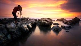 Playa de Sawarna 24 DE MAYO DE 2016 Fotógrafo que toma la foto de la puesta del sol en la playa de Sawarna, Indonesia Fotos de archivo