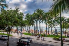 Playa de Waikiki, coches, visitantes y cielo dramático Imágenes de archivo libres de regalías