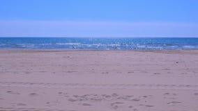Playa del arena de mar con agua azul y ondas espumosas en el día soleado almacen de video