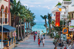 Playa del Carmem Beach Yucatan Mexico. The green and turquoise waters of Playa del Carmem beach and tourists on a street with shops and palm trees Stock Images
