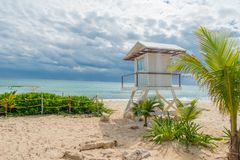 Playa del Carmen, Mexico - January 10, 2018: Outdoor view of safeguard hut in the beach during a sunny day with some. Dark clouds in the horizont of storm Stock Image
