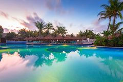 Luxury swimming pool scenery in Mexico. PLAYA DEL CARMEN, MEXICO - JULY 11, 2011: Luxury swimming pool scenery at RIU Yucatan Hotel in Playa del Carmen, Mexico Royalty Free Stock Photos