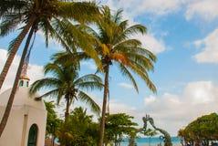 Playa del Carmen, Riviera Maya, Mexico:Tall coconut palms against the sky. Portal Maya, Maya gates at the entrance to the beach.  royalty free stock photography