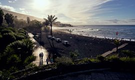 Playa del Castillo, Puerto de la Cruz, Tenerife, Spain - October 30, 2018: People captured walking in the sunset at the black sand stock photography