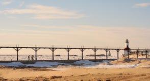 Playa del invierno con la gente que camina hacia el faro Imagen de archivo