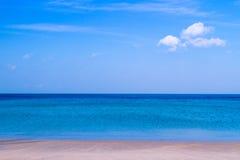 Playa del mar con el cielo azul y arena amarilla y algunas nubes sobre el la foto de archivo