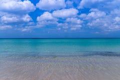 Playa del mar con el cielo azul y arena amarilla y algunas nubes sobre el la imagenes de archivo
