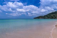 Playa del mar con el cielo azul y arena amarilla y algunas nubes sobre el la fotografía de archivo