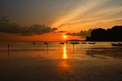 Playa del mar de la puesta del sol con las siluetas del barco de la cola larga Fotografía de archivo libre de regalías