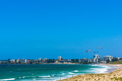 Playa del océano con horizonte de las personas que practica surf y de la ciudad de la cometa adentro Imagen de archivo