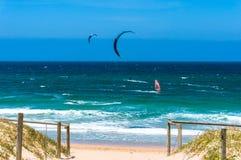 Playa del océano con las personas que practica surf de la cometa y del viento en a Imágenes de archivo libres de regalías