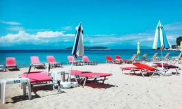 Playa del océano con las sillas rojas del sundeck imagenes de archivo