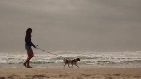 Playa del perro de la mujer que camina joven