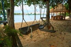 Playa del río con la choza de la paja y oscilación en Kampot Camboya imagenes de archivo