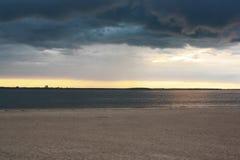 Playa del río y aguas oscuras del río en la puesta del sol Imagenes de archivo