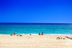 Playa del verano con la gente que toma el sunbath en la arena de oro No cuervo Foto de archivo