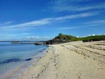 Playa delante de una pequeña colina rocosa Imagenes de archivo