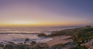 playa e iglesia bajo luz del orang de la puesta del sol fotografía de archivo