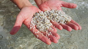 Playa en Cerdeña En las manos de las pequeñas piedras integradas por granos coloreados del cuarzo Foto de archivo